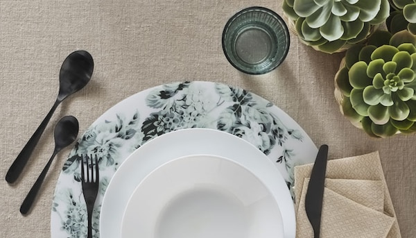 White place setting with green floral placemat and black utensils
