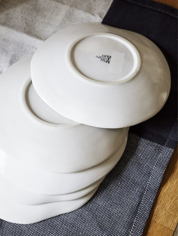 White plates stacked on a tea towel.
