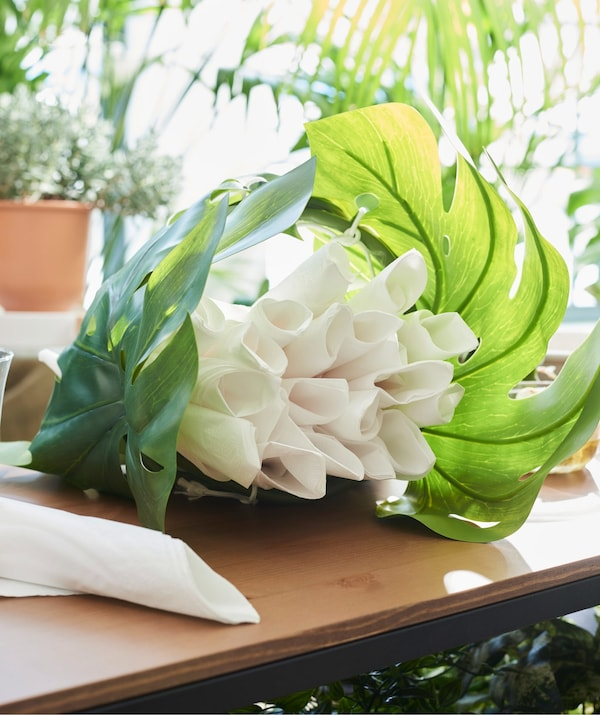 White rolled up napkins surround by IKEA SMYCKA green artificial leaves, to represent a bunch of flowers.