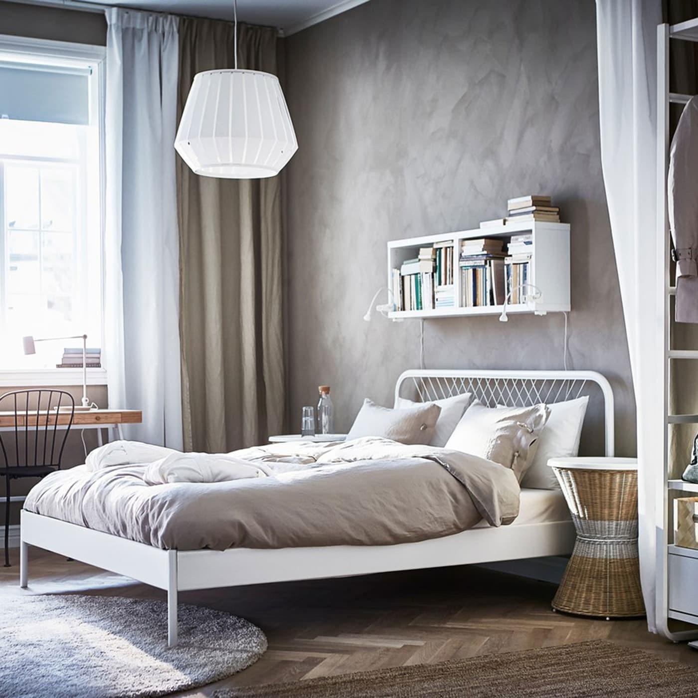White Scandinavian styled IKEA NESTTUN wired bedframe in a crisp room with beige walls and an open air wardrobe.
