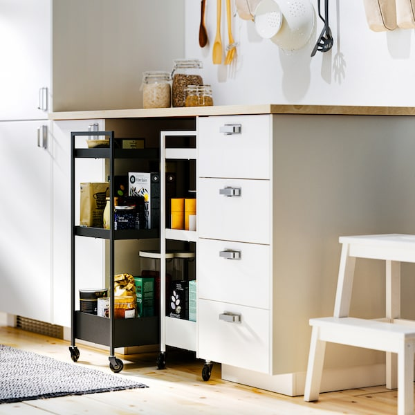White SEKTION base cabinets and an EKBACKEN worktop with NISSAFORS trolleys – a black and a white – in a recess below.