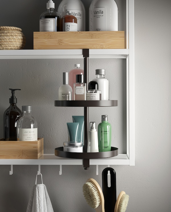 White shelving unit with hooks and a black swivel shelf. Trays, boxes, perfumes, lotions and more are on the shelves.