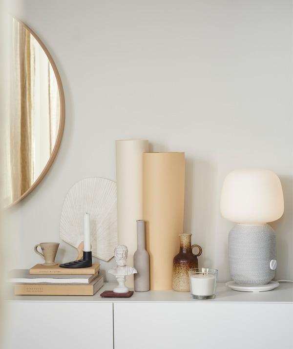White sideboard with a decorative display of books, a candle, a SYMFONISK Wi-Fi speaker lamp, pottery and a mirror on the wall.