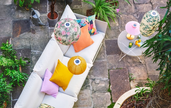 White sofa on a natural-stone patio. Cushions on the sofa and pendant lamps above it, all in bright colours and patterns.