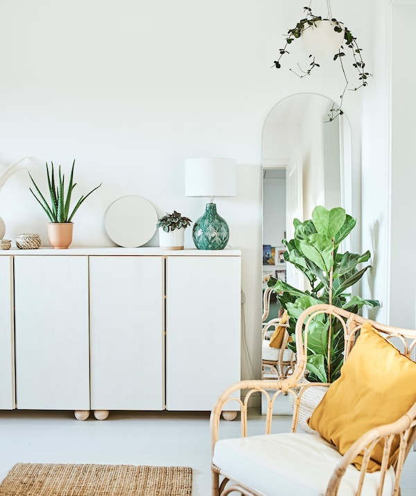 White stained cupboards with plants, a mirror and green lamp on the top, an arch-shaped mirror is framed by a hanging plant.