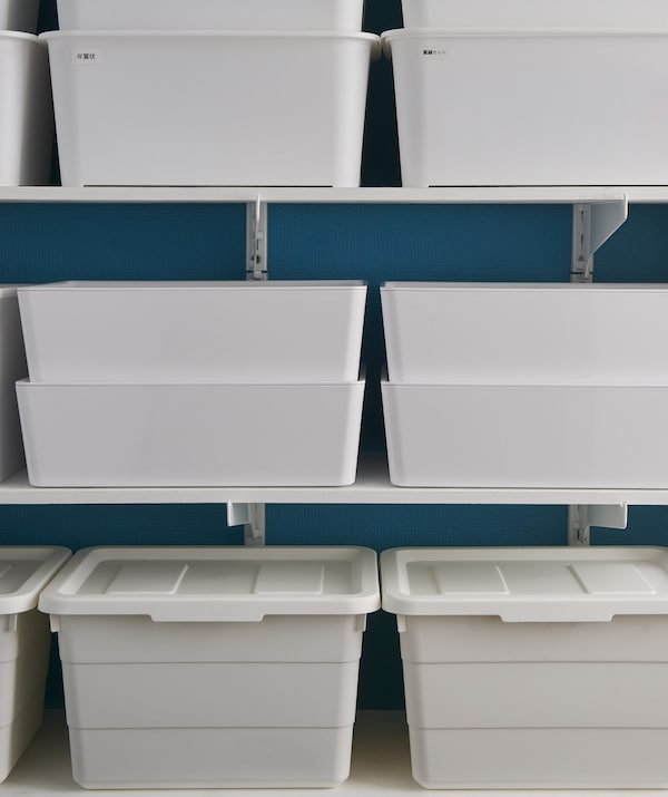 White storage boxes stacked on shelves.