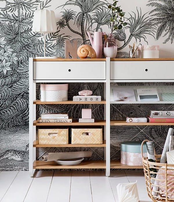 White storage rack with wooden shelves and a unit with home accessories against a wall with jungle-print wallpaper