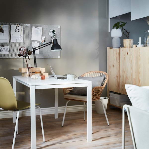 White table with mounted work lamp and scattered study accessories. Next to the table is a set of IVAR cabinets.