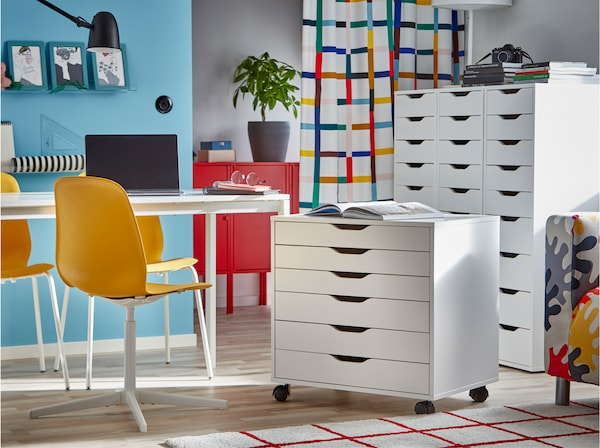 White table, yellow chairs, one large white drawer unit and one smaller on castors that's rolled to a white table.