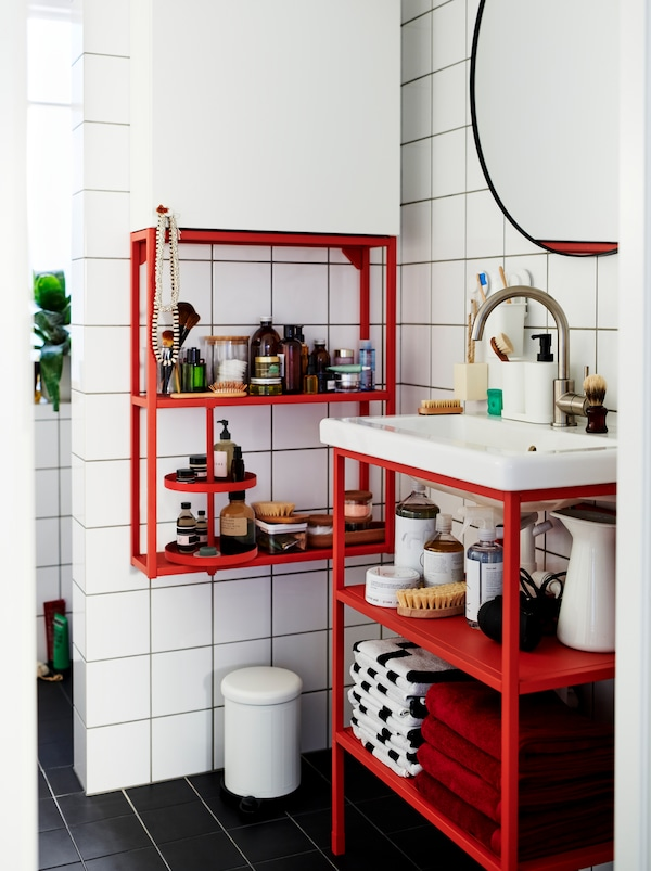 White-tiled bathroom furnished with a mix of red and white ENHET modules, holding decorations and accessories.