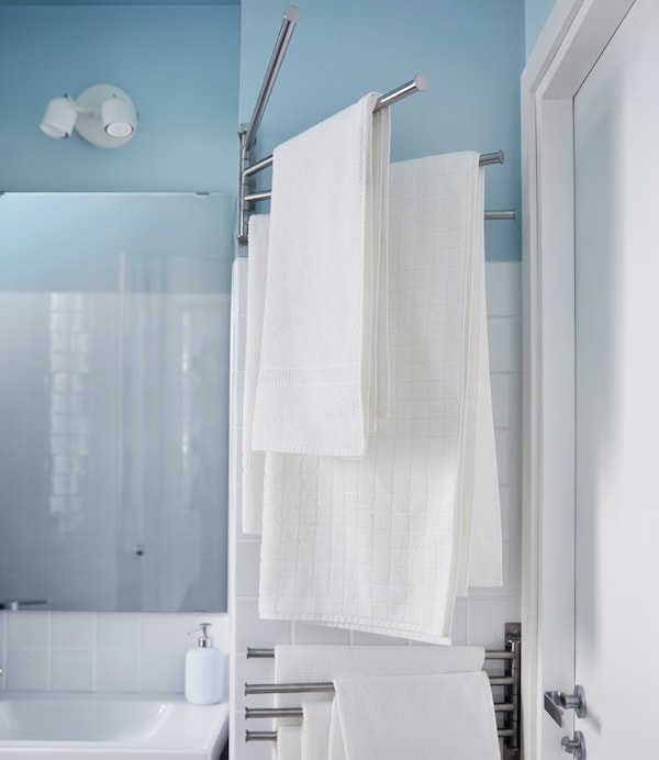 White towels hang on a towel rack that swings in and out from the wall in this small bathroom.