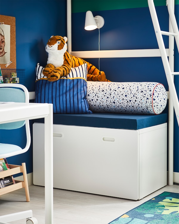 White toy storage placed under a white loft bed where you can sit thanks to comfortable cushions on top.