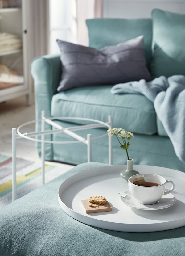 White tray taken off IKEA GLADOM white tray table and placed on a green sofa footstool, holding a teacup and a small sweet cracker.