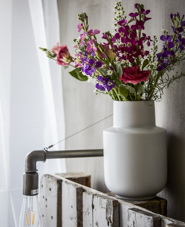 White vase with flowers.