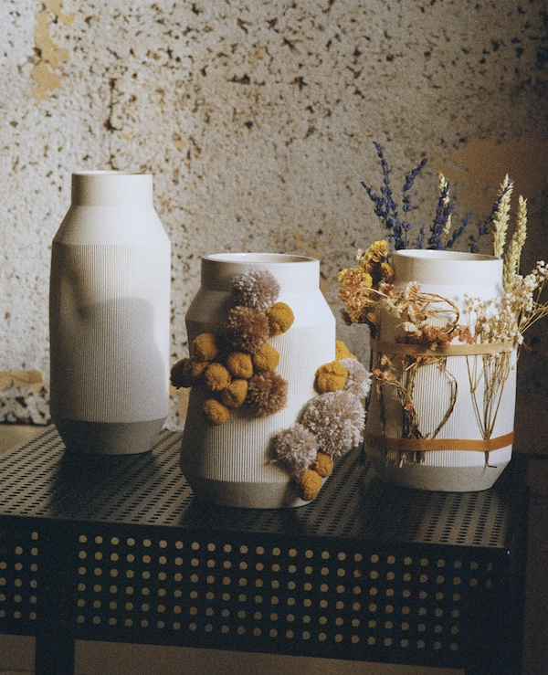 White vases covered with dried flowers.