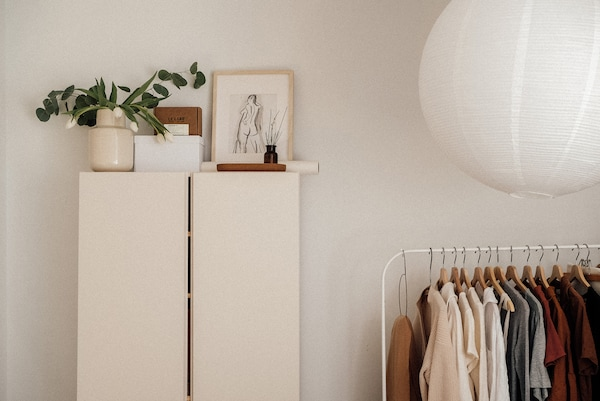 White wardrobe and MULIG clothes rack in white, holding neutrally coloured clothing on hangers.
