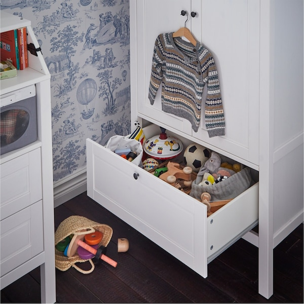 White wardrobe with a bottom drawer that's open and shows stored toys. A children's sweater hangs above on the door's knob.