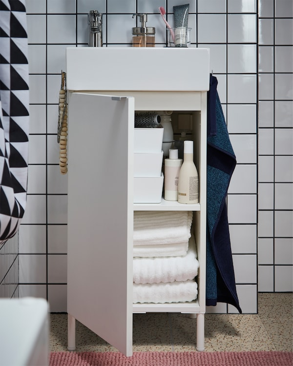 White wash basin cabinet with towels inside, a pink bath mat on the floor and a dark blue towel on the side of the cabinet.