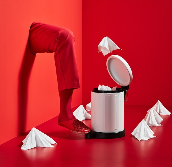 White waste bin in front of a red background