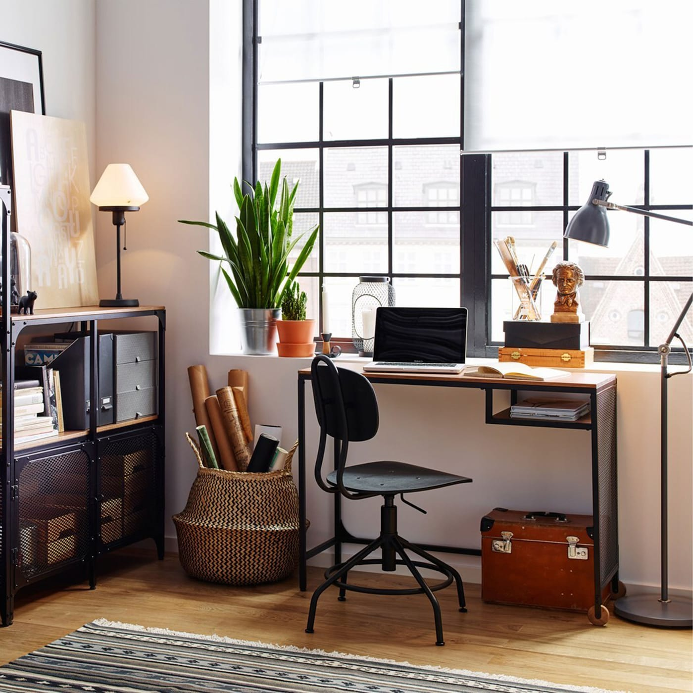 White workspace with wood floors and industrial style FJÄLLBO black metal and wood shelving and desk, by a window.