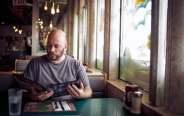 William sits in a diner looking at a menu.