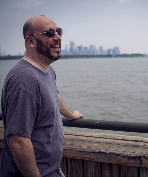 William stands looking across the water with a city skyline in the background.
