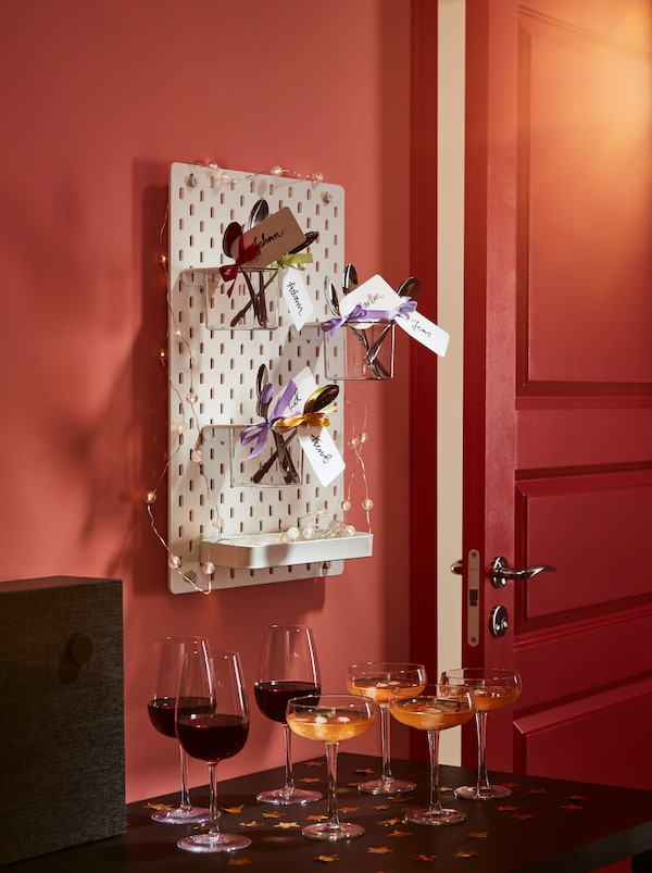 Willkommensgetränke auf einem Beistelltisch. Darüber hängt eine geschmückte SKÅDIS Lochplatte mit Behältern, in denen sich DRAGON Löffel befinden. An jedem Löffel ist eine Schleife und ein Namensschild angebracht.