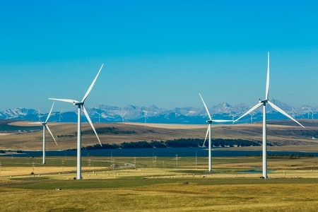 Windmills on the prairies with mountains in the background