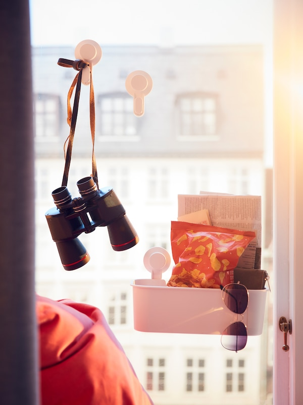 Window overlooking multistory facades. TISKEN suction-cup hooks and basket on the glass hold binoculars and snacks.