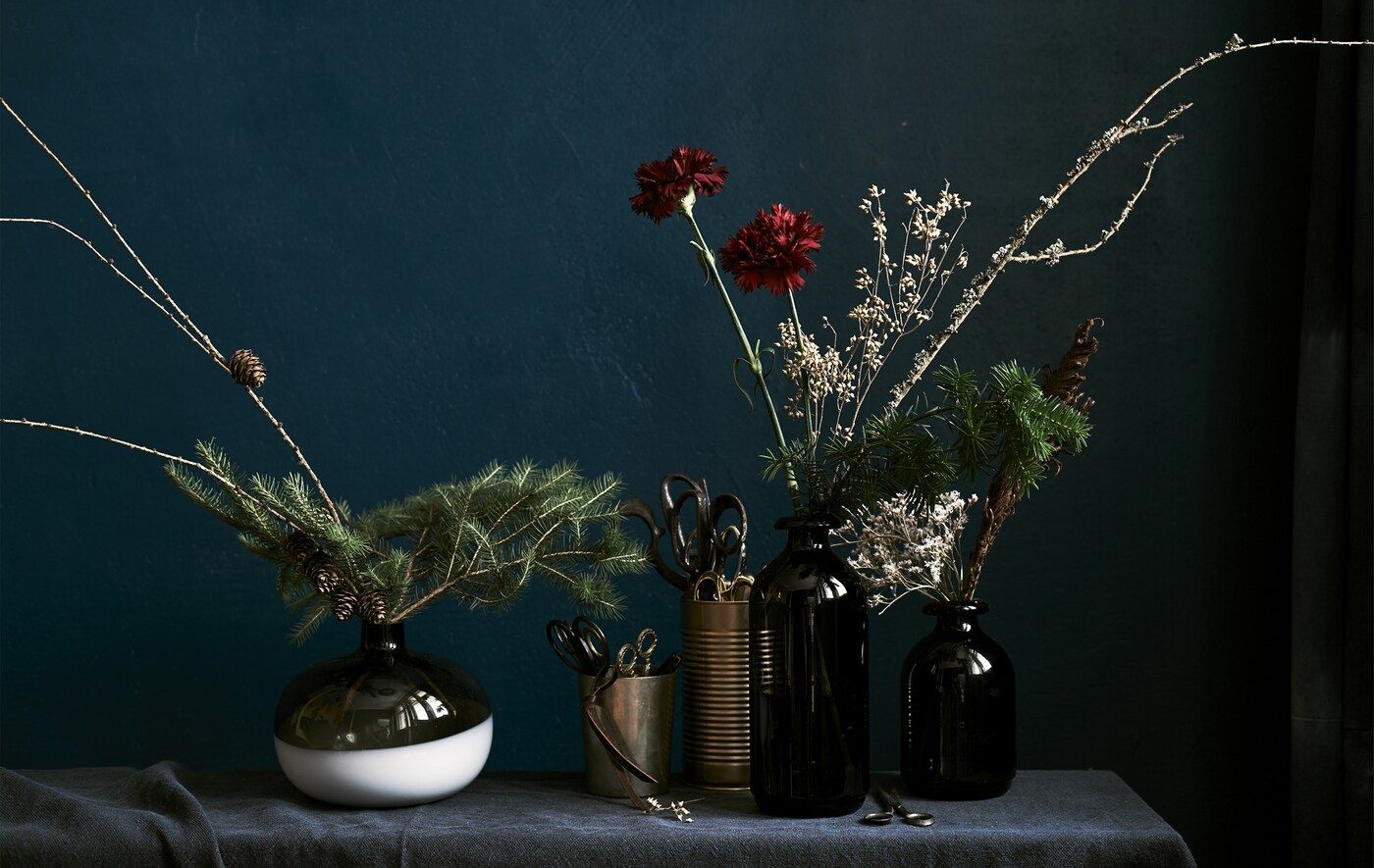Winter floral displays made up of green sprigs, dry branches and fresh flowers arranged in dark vases set against a dark cloth background.