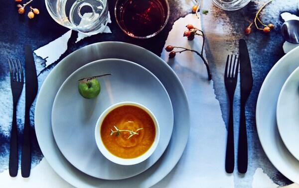 Winterlich gedeckter Tisch mit einer blauen Tischdecke, blauen Tellern & einer Suppe auf den Tellern