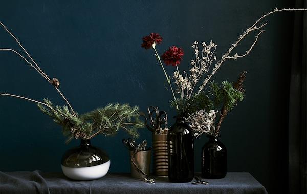 Wintery floral displays made from fresh sprigs, dried branches and flower stems in dark vases against a dark backcloth.