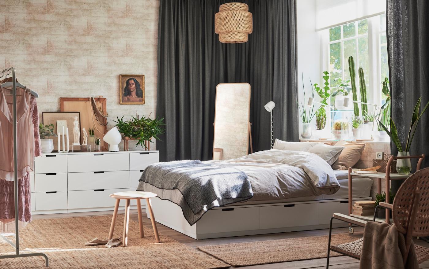 Wit bed met laden in een grote slaapkamer met zichtbare bakstenen, grijze gordijnen en jute tapijten