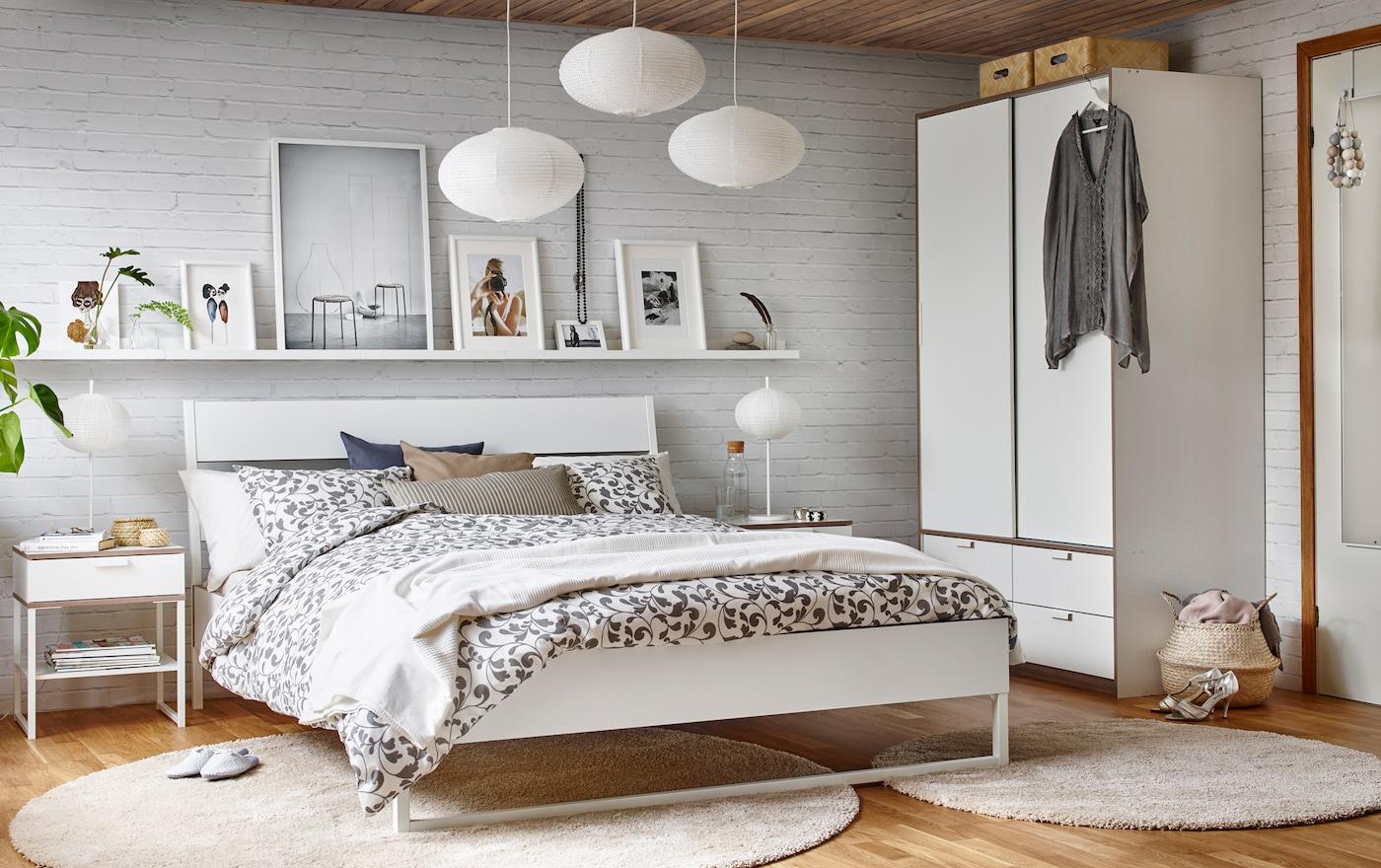 Wit met lichgrijze slaapkamer met een houten vloer, witte bakstenen muur en een tweepersoonsbed