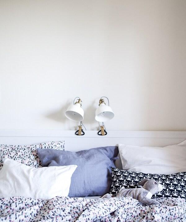 Witte slaapkamer met twee lampen aan het bedframe vastgeklemd