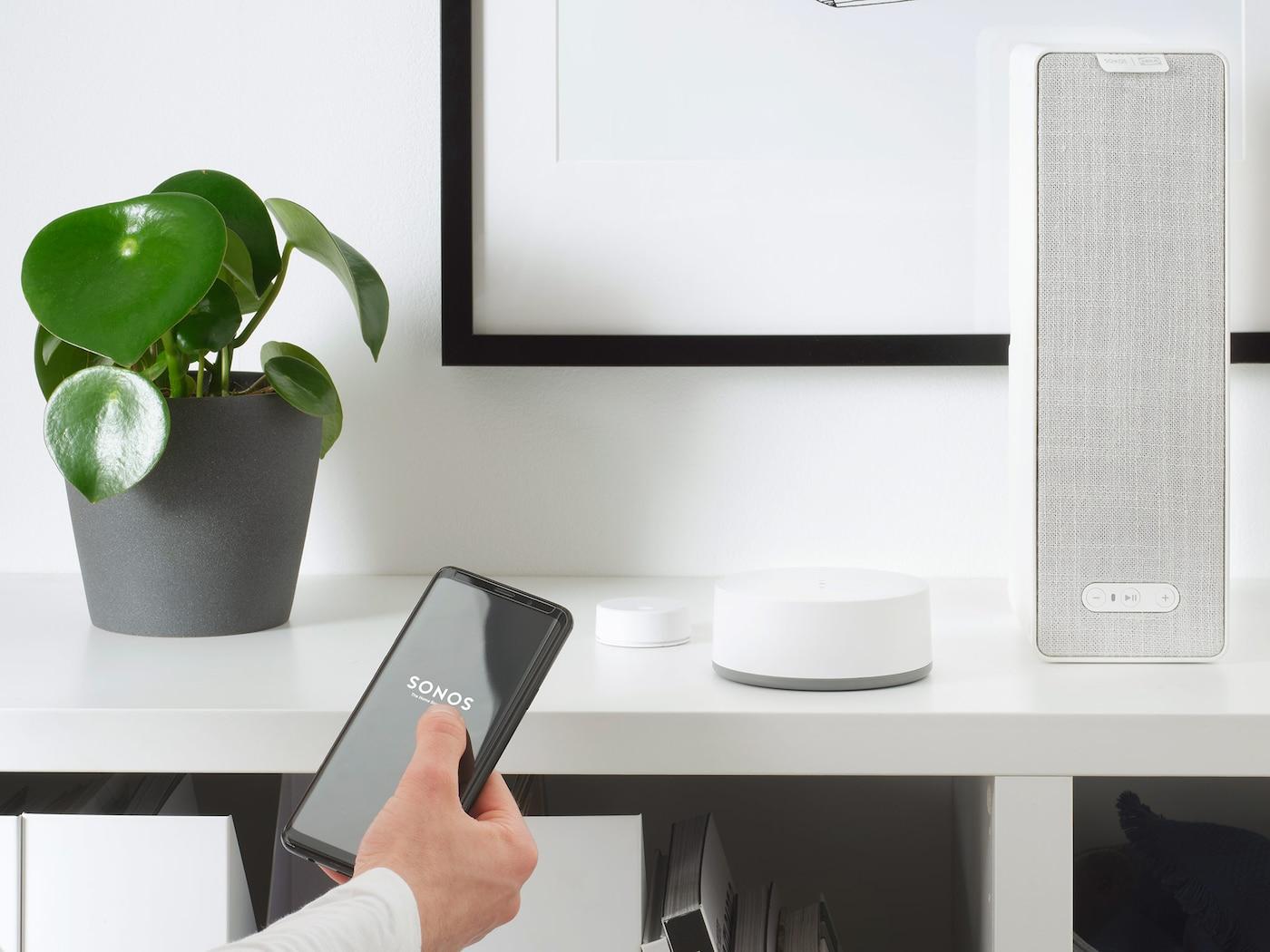 Witte SYMFONISK wifispeaker staat op een boekenkast in een woonkamerinterieur.