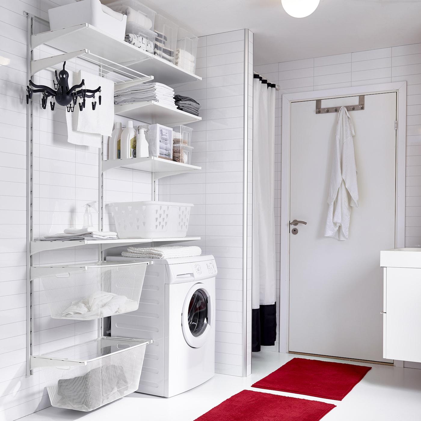 Witte wasruimte met rode badmatten en ALGOT systeem van IKEA