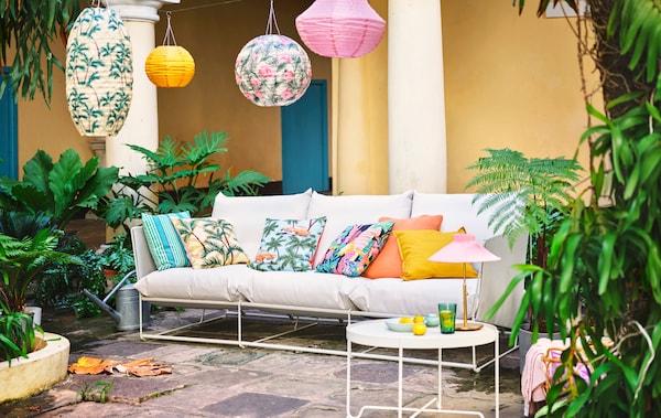 Witte zitbank op een natuurstenen patio. De kussens op de zitbank en de hanglampen erboven hebben allemaal vrolijke kleuren en patronen.