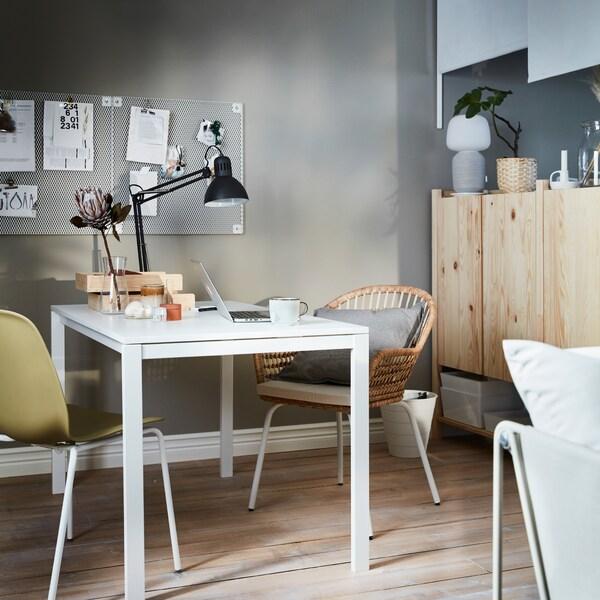 ワークランプが取り付けられ、勉強道具が散らばっているホワイトのテーブル。テーブルの隣にはIVAR/イーヴァル キャビネットセットが置かれています。