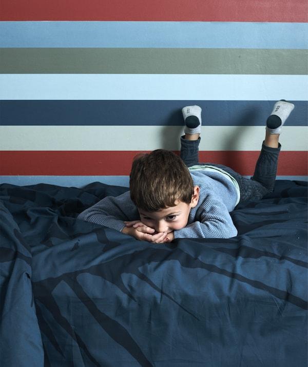 ولد مستلقٍ على سرير عليه شراشف باللون الأزرق الداكن وورق جدران مخطط في الخلف.