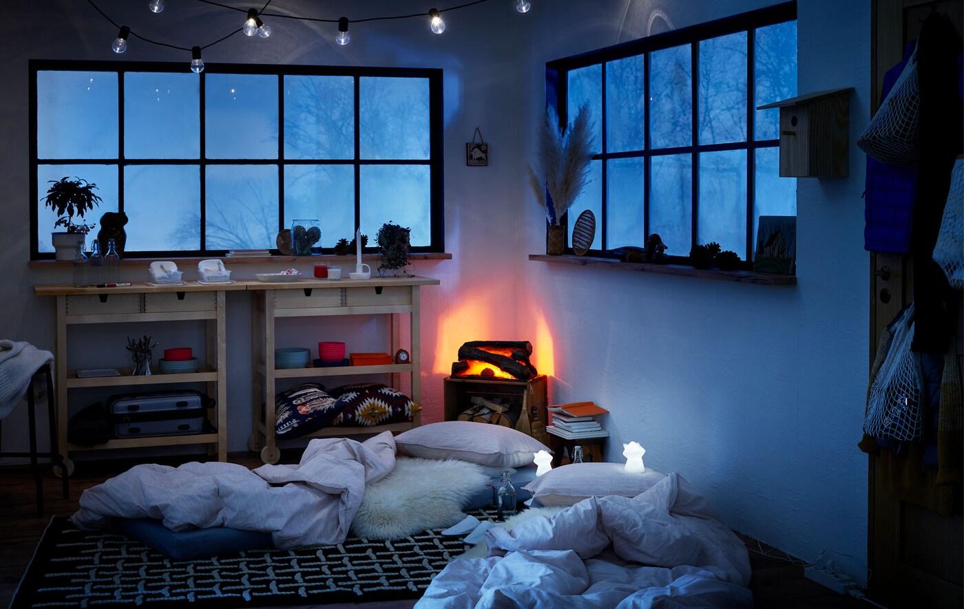 Wnętrze chatki w zimowym stylu, materace na ziemi służące za prowizoryczne łóżka, nocne lampki LED stojące obok.