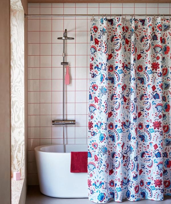 Wnętrze łazienki z bogato zdobioną zasłoną prysznicową zawieszoną przy wannie z prysznicem.