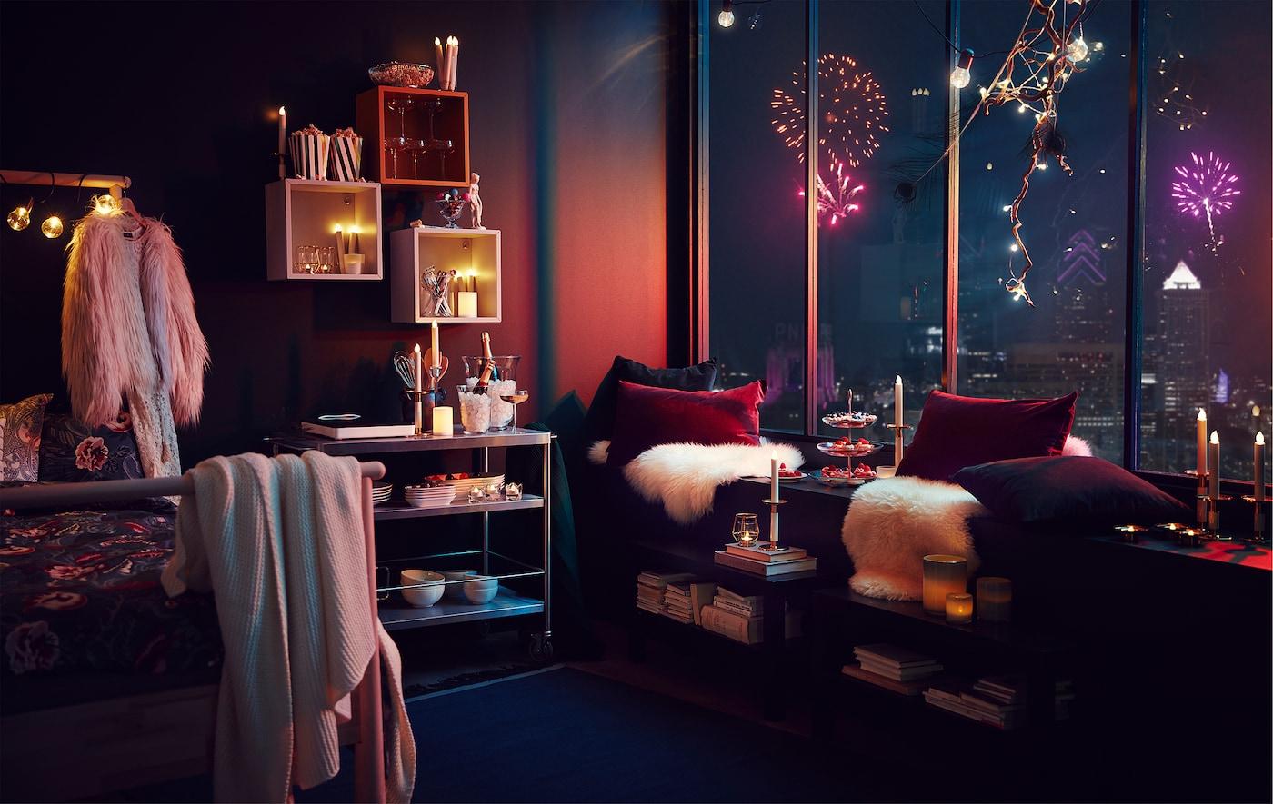 Wnętrze mieszkania z imprezowymi dekoracjami i oświetleniem; fajerwerki nad miastem widoczne przez wysokie okna.