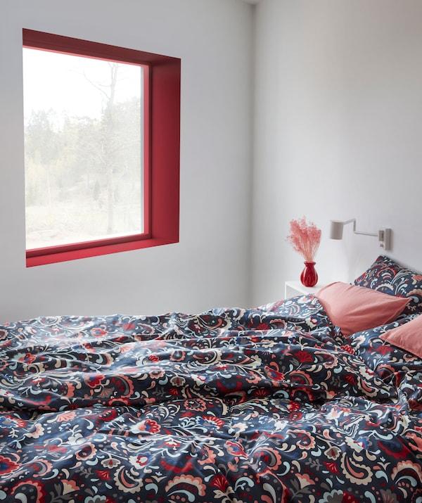 Wnętrze sypialni i łóżko z pościelą w jaskrawych kolorach, ozdobioną tradycyjnym szwedzkim wzorem kurbits.