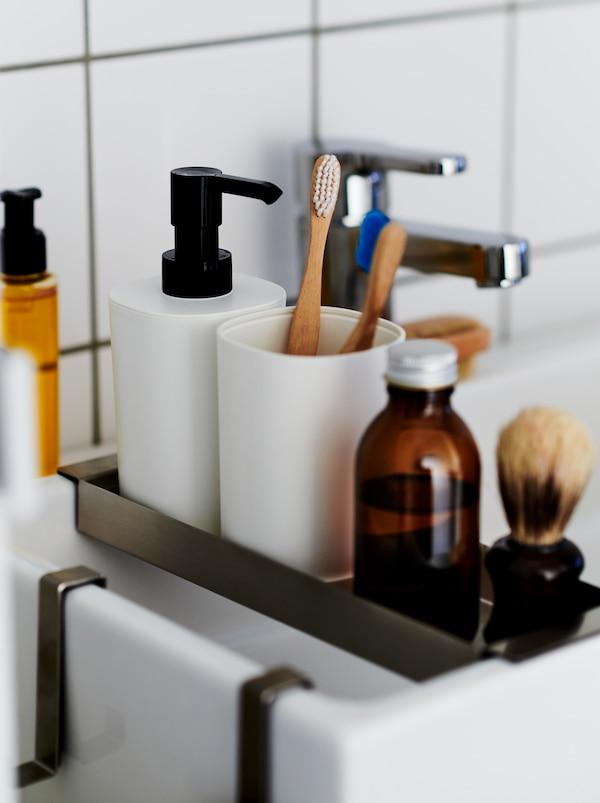 Wnętrze wyłożonej białymi płytkami łazienki z wąską półeczką ułożoną na umywalce LILLÅNGEN, na której ustawiono zestaw łazienkowy STORAVAN.