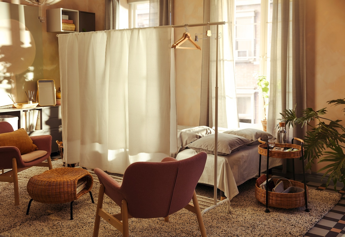 Wohnraumeinrichtung, bei der ein großes Bett hinter einem Raumteiler aus einem RIGGA Garderobenständer und VÅRELD Tagesdecken steht
