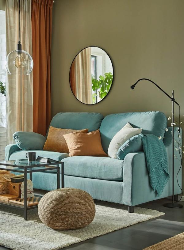Wohnzimmer mit blauem Sofa und Wandschränken. Ein heller Teppisch und ein edler Galstisch stehen in der Mitte des Raumes.