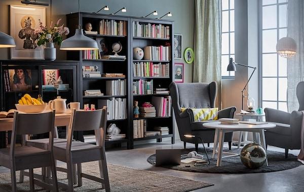 Wohnzimmer mit dunklem Bücherregal, einem Ohrensessel und Esstisch und zu jedem Bereich die passende Beleuchtung.