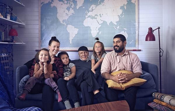 Wohnzimmer mit einer Familie auf einem blauen Sofa, mit Beleuchtung & einer Weltkarte an der Wand.