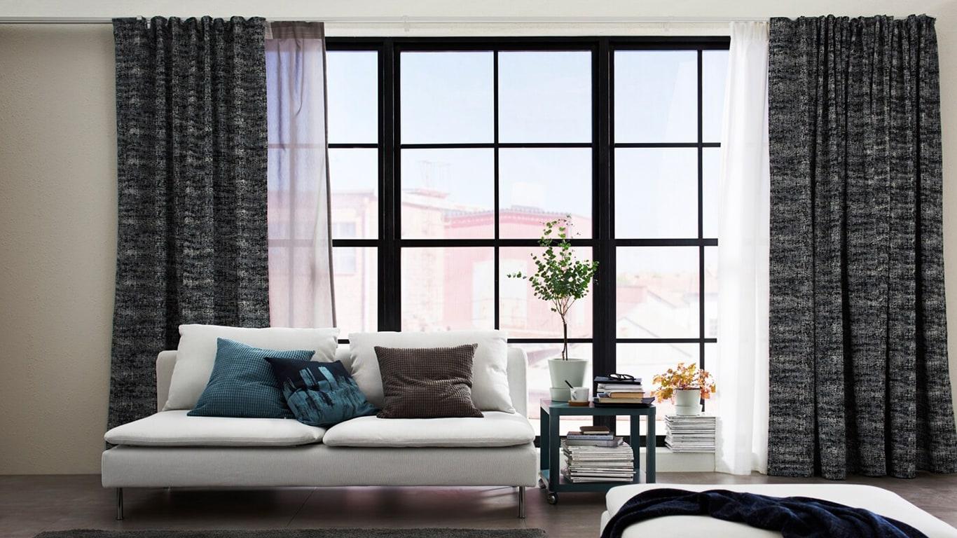 Wohnzimmer mit großen Fenstern, eingerichtet mit verdunkelnden SOLIDASTER Gardinenschals